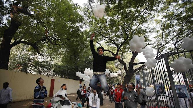 FILE - In this Saturday, Nov. 16, 2013 file photo, a Greenpeace activist jumps to catch a thread tied to balloons during a protest against the imprisonment of the group's activists and freelance journalists in New Delhi, India. India is cracking down on foreign-funded charities after receiving an internal report alleging they are costing the country up to 3 percent of its GDP by rallying communities against polluting industries. (AP Photo/Altaf Qadri, File)