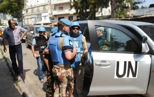 A photo released by the state-run Syrian Arab News Agency (SANA) shows a team of United Nations observers touring the Syrian town of al-Haffe with an official Syrian security escort on June 14. The United Nations monitoring mission in Syria will remain suspended because of the mounting conflict, a top UN official told the UN Security Council on Tuesday