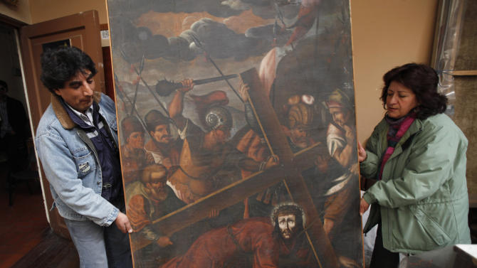"""In this Aug. 21, 2013 file photo, workers from the Culture Ministry display a recovered 18th century painting by an anonymous artist depicting Jesus in La Paz, Bolivia. This painting titled """"Jesus con la Cruz a Cuesta"""" was stolen from the San Pedro de la Paz church in Bolivia on June 11, 2003, and recovered in the Peruvian capital of Lima in April 2005. Increasingly bold thefts plague colonial churches in remote Andean towns in Bolivia and Peru, where religious and civil authorities say cultural treasures are disappearing at an alarming rate. (AP Photo/Juan Karita)"""