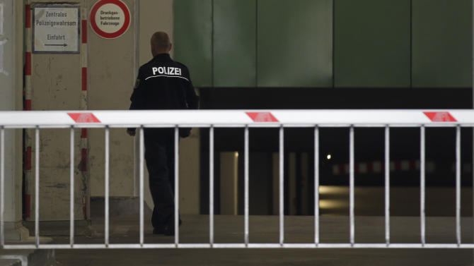 A police officer walks inside the car gateway of the central police detention facility of Berlin where Luka Rocco Magnotta is  being held in Berlin, Germany, Tuesday, June 5, 2012. Luka Magnotta, 29, a Canadian porn actor suspected of murdering and dismembering a Chinese was arrested on Monday at an Internet cafe in a working-class district of the German capital, where he had been reading media coverage of himself. A cafe employee recognized Magnotta from a newspaper photo and flagged down a police car. The white child left reads 'Centrap Police Detention'. (AP Photo/Markus Schreiber)