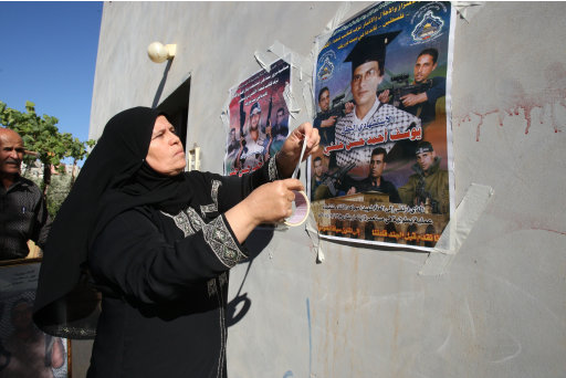 A woman hangs up a poster of Palestinians she says were killed by Israeli troops, outside a house in the West Bank village of Beit Furik near Nablus, Monday, July 4, 2011.  Israeli and Palestinian officials say they have reached a deal to transfer the remains of 84 Palestinian militants from an Israeli grave site to the West Bank. The Palestinian Civil Affairs Department published the names of the dead Palestinians on Monday.  It is not yet known if the people portrayed in poster are those who's remains are being returned. (AP Photo/Nasser Ishtayeh)