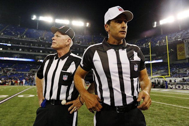 Referee Gene Steratore, right, and back judge Bob Waggoner, left, look around the field before an NFL football game between the Baltimore Ravens and Cleveland Browns in Baltimore, Thursday, Sept. 27,