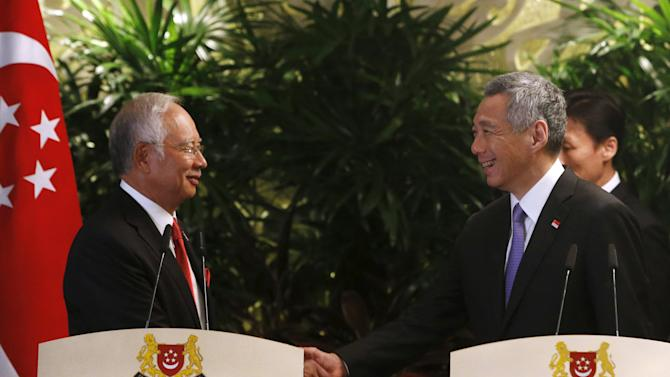 Singapore's Prime Minister Lee Hsien Loong shakes hands with Malaysian counterpart Najib Razak after a news conference in Singapore