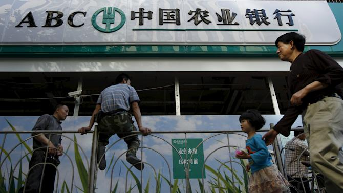File picture of people walking past a branch of Agricultural Bank of China in Shanghai