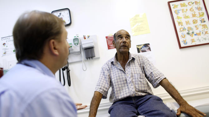 Patient Luis Gutierrez, right, talks with Dr. Javier Hiriart at Camillus Health Concern, Wednesday, June 27, 2012, in Miami. Camillus is a private, non-profit organization that provides health care to the homeless and poor in Miami-Dade County. Presidential candidates, governors of virtually every state, insurers with billions at stake, companies large and small and countless millions of Americans concerned about their own medical care and how they'll pay for it are awaiting a Supreme Court ruling expected Thursday on whether or not the Affordable Care Act passes the test of constitutionality.(AP Photo/Lynne Sladky)