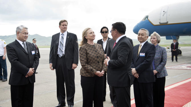 FILE - In this Monday, July 9, 2012 photo, U.S. Secretary of State Hillary Rodham Clinton, third from left, speaks with Mongolian Minister of Foreign Affairs and Trade Gombojav Zandanshatar, third from right, upon arrival at Ulan Bator Airport, Mongolia. If diplomatic achievements were measured by the number of countries visited, Hillary Rodham Clinton would be the most accomplished secretary of state in history. Since becoming secretary of state in 2009, Clinton has logged 351 days on the road, traveled to 102 countries and flown a whopping 843,839 miles, according to the State Department. (AP Photo/Brendan Smialowski, Pool, File)