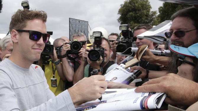 Formula One Red Bull driver and world champion Sebastian Vettel of Germany signs autographs after he arrived at Albert Park track for the Australian Grand Prix in Melbourne, Australia, Thursday, March 14, 2013. The season-opening race is scheduled for this weekend. (AP Photo/Rob Griffith)