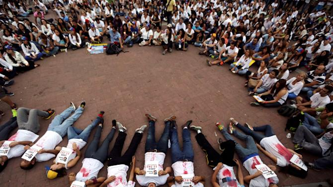 Demonstrators lie on the ground holding statistics about the people murdered in the 14 years of Chavista government, at a protest in Caracas, Venezuela, Friday, March 7, 2014. Venezuela is coming under increasing international scrutiny amid violence that most recently killed a National Guardsman and a civilian. United Nations human rights experts demanded answers Thursday from Venezuela's government about the use of violence and imprisonment in a crackdown on widespread demonstrations. (AP Photo/Fernando Llano)