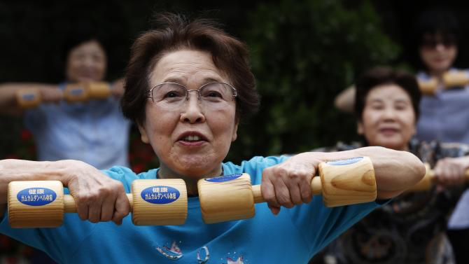 "People use wooden dumbbells during a health promotion event to mark Japan's ""Respect for the Aged Day"" at a temple in Tokyo's Sugamo district"
