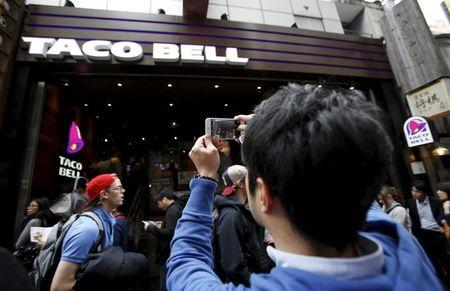 Man takes picture of first Taco Bell fast-food restaurant in Japan at Tokyo's Shibuya shopping district