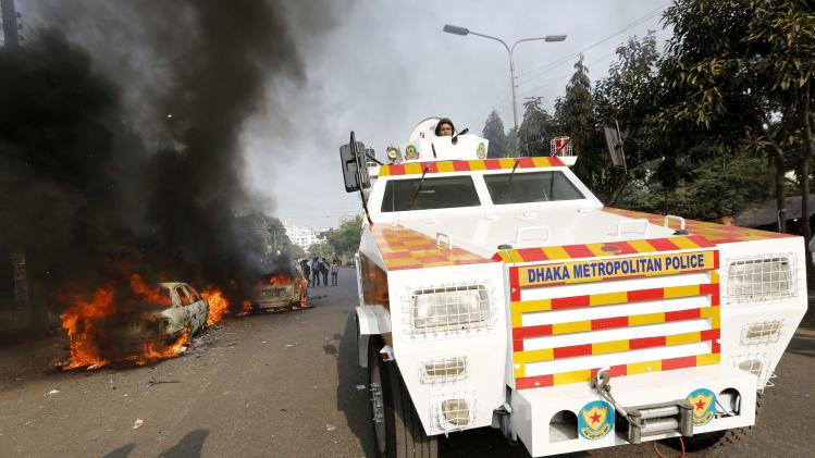 A police vehicle goes past vehicles that were torched by Jamaat-e-Islami party activists during clashes with police in Dhaka