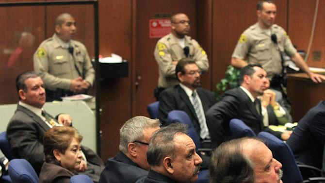 Five former Bell City elected officials listens to the judge as a guilty verdict is read in their trial on Wednesday, March 20, 2013, in Los Angeles.  The five former elected officials were convicted of multiple counts of misappropriation of public funds, and a sixth defendant was cleared entirely. Former Mayor Oscar Hernandez and co-defendants Teresa Jacobo, George Mirabal, George Cole, and Victor Belo were all convicted of multiple counts and acquitted of others.  The charges against them involved paying themselves inflated salaries of up to $100,000 a year in the city of 36,000 people, where one in four residents live below the poverty line.   (AP Photo/Los Angeles Times, Irfan Khan, Pool)