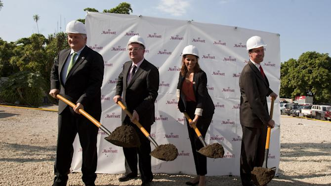FILE - In this Dec. 19, 2012 file photo, Denis O'Brien, chairman of Digicel Group, left, Digicel Group CEO Colm Delves, second from left, Haiti's Tourism Minister Stephanie Balmir Villedrouin, second from right, and Arne Sorenson, president and CEO of Marriott International participate in a groundbreaking ceremony for the construction of a Marriott hotel in Port-au-Prince, Haiti. For Nickson Toussaint, who returned to Haiti from Washington, D.C. with dreams of opening a small hotel along the coast north of the country's capital, the snags he's hit reflect a system that favors big, multinational companies such as Marriott International or Best Western. (AP Photo/Dieu Nalio Chery, File)