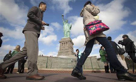 People walk past the Statue of Liberty on Liberty Island in New York