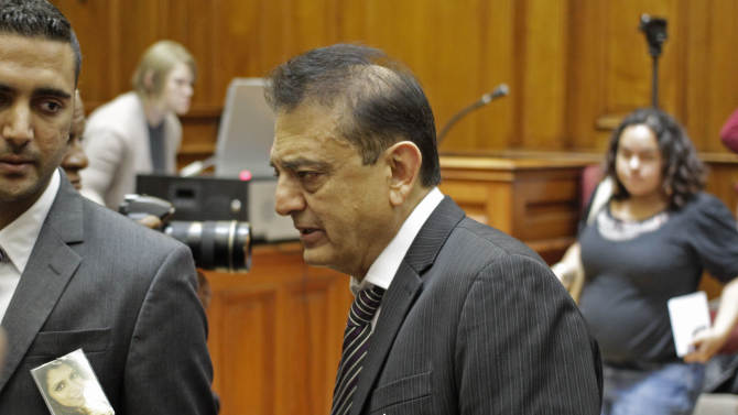 """Vinod Hindocha, center, arrives in court with a photo of his slain daughter Anni Dewani,  on his jacket in Cape Town, South Africa, Wednesday, Dec. 5,  2012. A South African judge sentenced the triggerman in the 2010 honeymoon slaying of a Swedish bride to life in prison Wednesday, calling the shooter """"a merciless and evil person"""" who deserved the maximum punishment for his crime. Prosecutors say the newlywed's British husband orchestrated the November 2010 killing. Judge Robert Henney did not hold back his contempt while sentencing Xolile Mngeni for the killing of 28-year-old Anni Dewani. Henney said that the shooter showed no remorse. (AP Photo/Schalk van Zuydam)"""