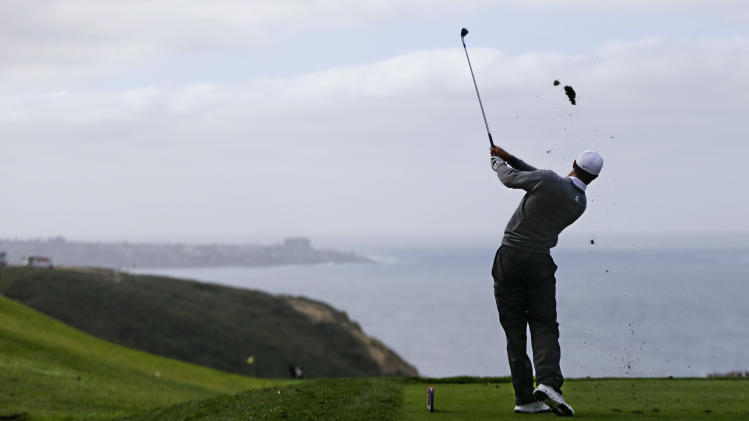 Tiger Woods hits his tee shot on the par three third hole on the South Course at Torrey Pines during the third round of the Farmers Insurance Open PGA golf tournament Sunday, Jan. 27, 2013, in San Diego. (AP Photo/Lenny Ignelzi)