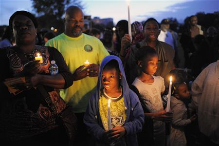 A boy wears a hooded sweatshirt, as he joins other attendees in a candlelight vigil at the exact moment when teenager Trayvon Martin was shot one year ago by neighborhood watch volunteer George Zimmerman in Sanford, Florida February 26, 2013. REUTERS/Brian Blanco