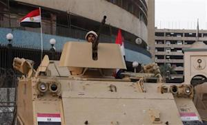 An Egyptian army soldier stands guard in front of the state television building in Cairo