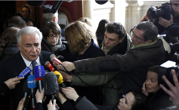 Dominique Strauss-Kahn, left, the former International Monetary Fund chief, addresses the media, as he files a lawsuit over a new book about a past relationship, Tuesday, Feb. 26, 2013,  in Paris. Dom