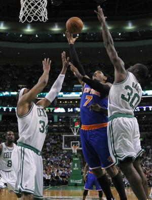 New York Knicks forward Carmelo Anthony (7) shoots against Boston Celtics forwards Paul Pierce (34) and Brandon Bass (30) during the first half in Game 4 of a first-round NBA basketball playoff series in Boston, Sunday, April 28, 2013. (AP Photo/Elise Amendola)