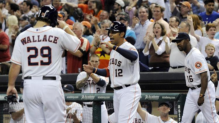 Houston Astros' Carlos Pena (12) welcomes Brett Wallace (29) to the dugout after the two scored on a Justin Maxwell two-RBI triple against the Texas Rangers in the fourth inning of a season-opening baseball game, Sunday, March 31, 2013, in Houston. (AP Photo/Pat Sullivan)