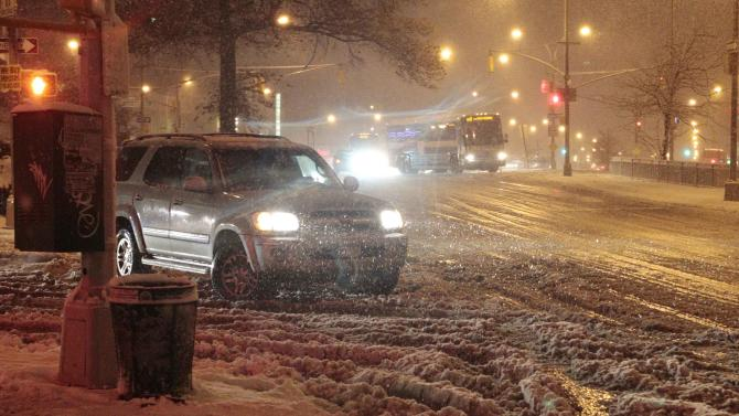 Cars navigate Queens Boulevard during a snow storm Wednesday, Nov. 7, 2012, in the Queens borough of New York. Coastal residents of New York and New Jersey faced new warnings to evacuate their homes and airlines canceled hundreds of flights as a new storm arrived Wednesday, only a week after Superstorm Sandy left dozens dead and millions without power.  (AP Photo/Frank Franklin II)