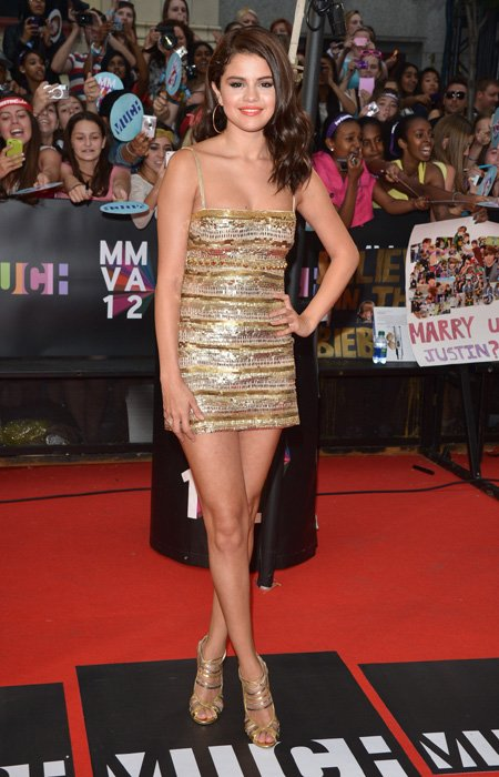 Teen queen Selena Gomez shows up in a gold mini-dress which shows off her killer legs, but where is her boyfriend, Justin Bieber? The dress certainly leaves not much to the imagination but what a way