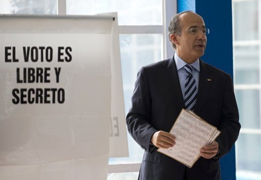 <p>Mexican President Felipe Calderon holds ballots during the general election on July 1. Calderon's conservative National Action Party (PAN) will formally request that electoral officials probe allegations of vote buying in Mexico's presidential election.</p>