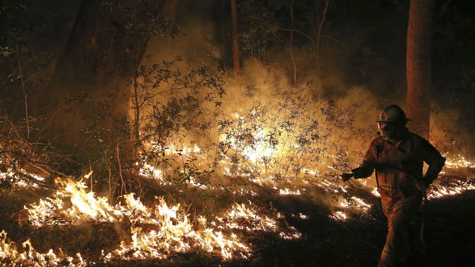 Firefighters control flames during hazard reduction in Bilpin 75 kilometers (46 miles) from Sydney in Australia, Wednesday, Oct. 23, 2013. Scores of Australians evacuated their homes in mountains west of Sydney on Wednesday as intensifying winds fanned wildfires and grounded the helicopters that were fighting them. (AP Photo/Rob Griffith)