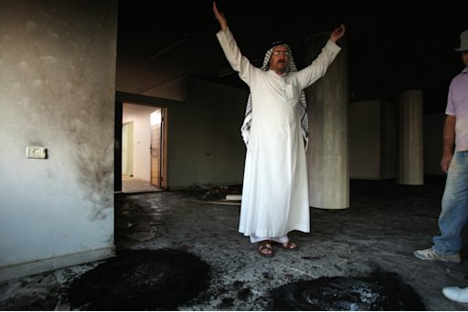 A Palestinian raises his hands as he and others inspect the damage inside a mosque torched and vandalized by arsonists in the West Bank village of Qusra, near Nablus, Monday, Sept. 5, 2011. Arsonists tossed two tires into the first floor study hall of a new mosque in the West Bank village of Qusra and set them ablaze, Israeli and Palestinian officials said Monday. No one claimed responsibility for the blaze. But the proximity to the Migron demolitions raised suspicion that the mosque fire was what settlers call