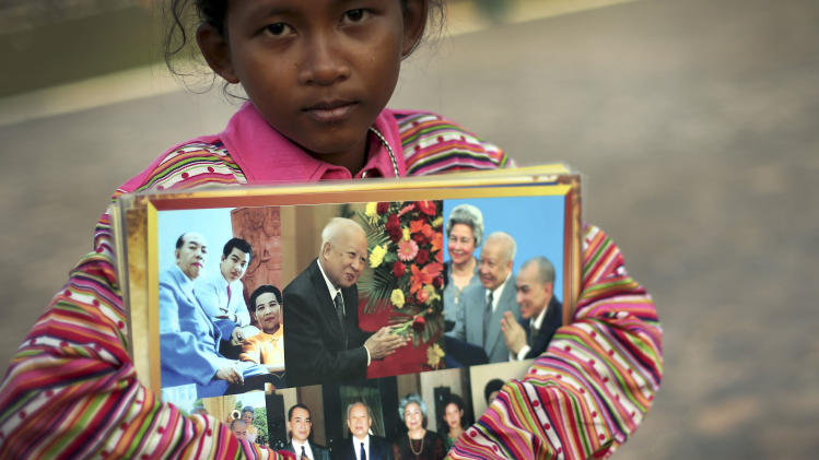A young girl sells photos of the late Cambodian King Norodom Sihanouk ahead of his funeral, Thursday, Jan. 31, 2013, in Phnom Penh, Cambodia. The body of Sihanouk who died on Oct. 15, 2012 at age 89, is scheduled to be cremated on Feb. 4, 2013. (AP Photo/Wong Maye-E)
