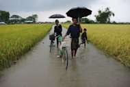 Muslim Rohingyas make their way through a flooded field to an Internally Displaced Persons camp on the outskirts of Sittwe. Surging sectarian violence in western Myanmar has left at least 64 people dead and scores more wounded, a local official says, casting a shadow over the government&#39;s reform drive