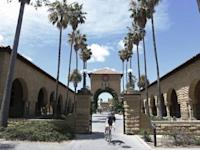 A cyclist exits the entryway to the Main Quad at Stanford University in Stanford