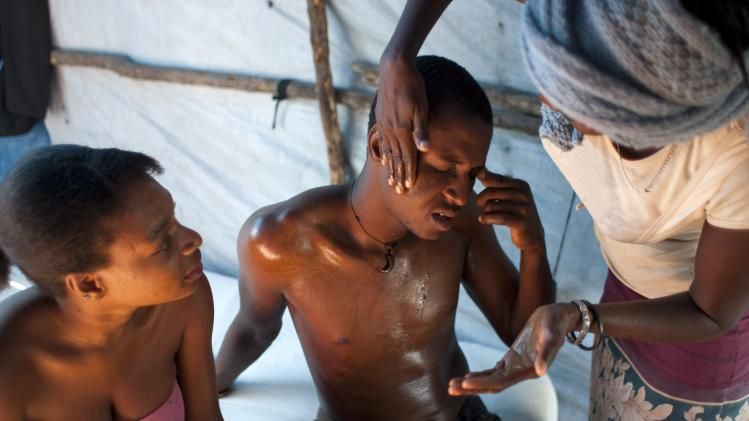 In this April 25, 2013 photo, Darlin Lexima is treated for injuries by family members at his home in Camp Acra in the Delmas district of Port-au-Prince, Haiti. Lexima says his injuries are from being beating by police with their batons and the butts of their pistols and rifles in the Delmas police station after he was arrested by police early April 15 when he was walking home from a disco club, as police were responding to residents at his camp who were protesting an earlier raid by motorcyclists who set fire to their homes. The motorcyclists came to Camp Acra hours after attorney Reynold Georges arrived with a judge and a police officer and told the some 30,000 people who had lost their homes in the 2010 earthquake that they were squatting on his land and had to leave, witnesses said. If they didn't vacate, he said he'd have the place burned down and leveled by bulldozers. (AP Photo/Dieu Nalio Chery)