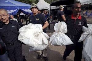 Forensic policemen carry body bags with human remains…