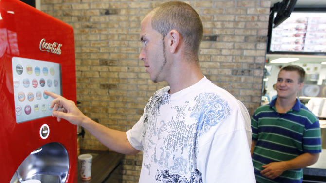 In this March 28, 2012 photo, Alex Dipasquale, left, selects a soda as his friend Lucas Kitt looks on at a Burger King restaurant in Miami. Burger King launches 10 menu items including smoothies, frappes, specialty salads and snack wraps in a star-studded TV ad campaign. It's the biggest menu expansion since the chain opened its doors in 1954. (AP Photo/Luis M. Alvarez)