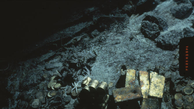 FILE - This 1989 file photo shows gold bars and coins from the S.S. Central America, a mail steamship, which sunk in a hurricane in 1857, about 160 miles off the North Carolina coast. Federal Judge Rebecca Beach Smith ruled Wednesday, July 9, 2014, that an Ohio company named Recovery Limited Partnership has salvage rights to the SS Central America. (AP Photo/File)