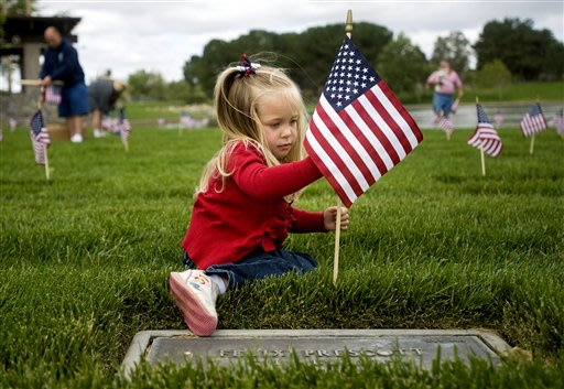 Mackenzie Griffith, 3, decorates a grave with a flag in honor of Memorial Day at Riverside National Cemetery, in Riverside County, Calif., on Saturday, May 26, 2012. Griffith was with a group of Orang
