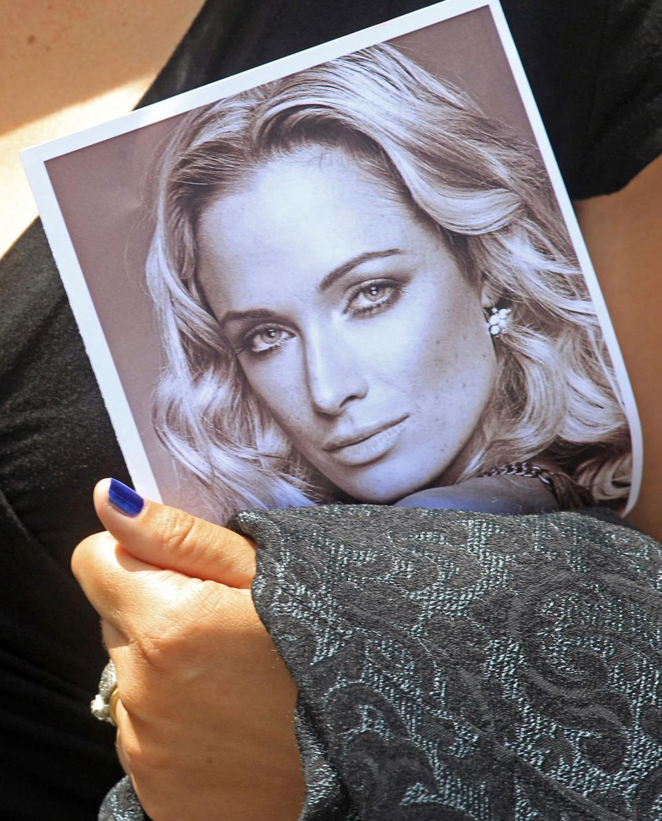 FILE - In this Tuesday, Feb. 19, 2013 file photo a mourner holds a funeral program with a portrait of Reeva Steenkamp, the late girlfriend of Oscar...