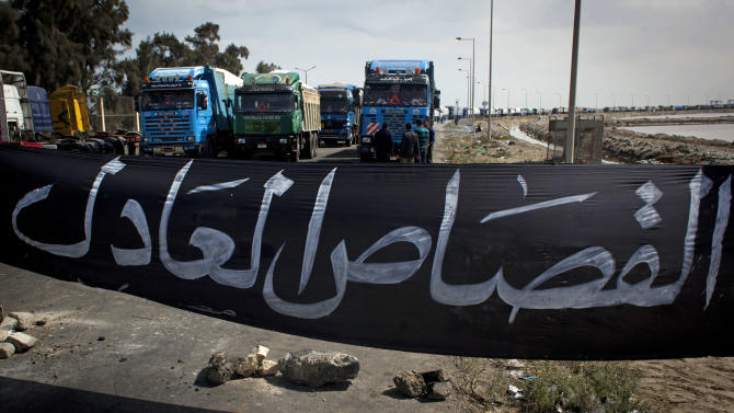 "Egyptian protesters, unseen, block a road preventing loaded trucks from leaving the port with a banner that reads in Arabic ""fair retribution,"" during a general strike, in Port Said, Egypt, Friday, Feb. 22, 2013. The most recent show of unrest in Egypt came in the restive city of Port Said, where a general strike entered its sixth day on Friday. Factory workers, activists and laborers have held street rallies that brought the coastal city on the northern tip of the Suez Canal to a halt, though shipping in the international waterway has not been affected. (AP Photo/Nasser Nasser)"