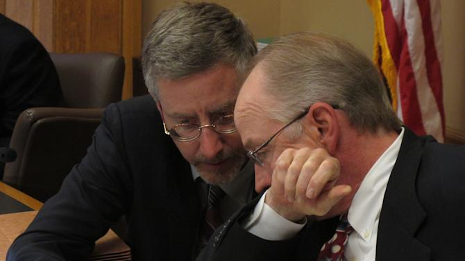 Chris Courtwright, left, principal analyst for the Kansas Legislative Research Department, and Gordon Self, right, an attorney on the Legislature's bill-drafting staff, confer as lawmakers negotiate over tax cuts, Monday, April 30, 2012, at the Statehouse in Topeka, Kan. Courtwright is the research staff's tax policy expert, and Self drafts legislation dealing with taxes. (AP Photo/John Hanna)