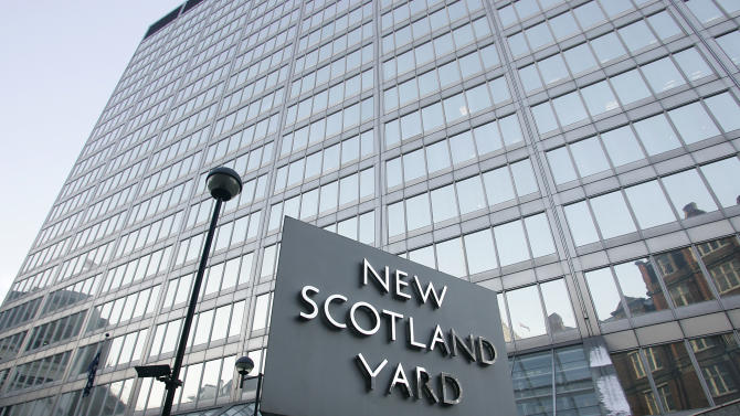 FILE - A Monday, Dec. 20, 2010 photo from files of New Scotland Yard, the headquarters building of the Metropolitan Police, with its sign. London's police force says it will move from its headquarters at New Scotland Yard as it faces making budget cuts of more than 500 million pounds ($800 million). Deputy Commissioner Craig Mackey told the mayor's office Tuesday, Oct. 30, 2012, that it plans to save 6.5 million pounds per year by moving to a smaller building. New Scotland Yard has been on London's Victoria Street since 1967. (AP Photo/Akira Suemori, File)