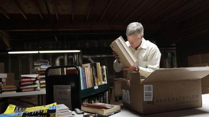 "In this July 21, 2011 photo, Mark, who did not give his last name, unpacks boxes of books at the Internet Archive's Physical Archive warehouse in Richmond, Calif. Saving a copy of every Web page ever posted sounds like an ambitious life's work, but Brewster Khale has decided digital isn't enough. The founder of the Internet Archive wants to expand his effort to provide ""universal access to all knowledge"" by preserving a physical copy of every book ever written. (AP Photo/Jeff Chiu)"