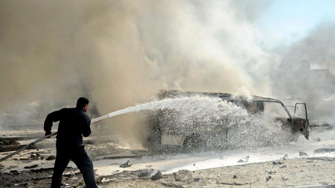 This photo released by the Syrian official news agency SANA, shows a Syrian fire fighter extinguishing burning cars after a huge explosion that shook central Damascus, Syria, Thursday, Feb. 21, 2013. A car bomb shook central Damascus on Thursday, exploding near the headquarters of the ruling Baath party and the Russian Embassy, eyewitnesses and opposition activists said. (AP Photo/SANA)