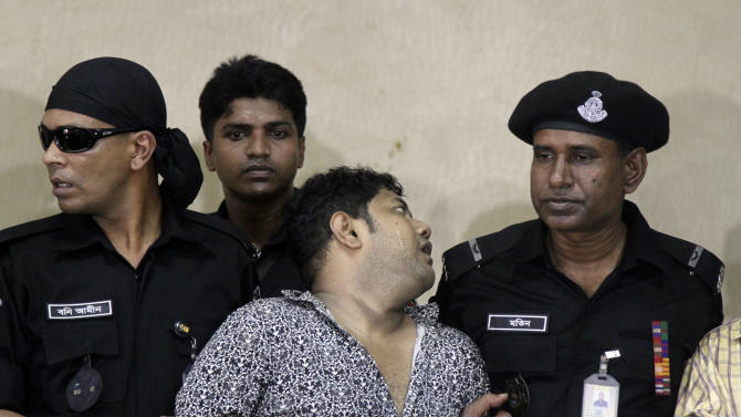 Mohammed Sohel Rana, center, the fugitive owner of an illegally-constructed building that collapsed last week in Bangladesh, reacts as he is produced before the media in Dhaka, Bangladesh, Sunday, April 28, 2013. Rana was arrested near the land border in Benapole in western Bangladesh, just as he was about to flee into India's West Bengal state, said Jahangir Kabir Nanak, junior minister for local government. (AP Photo/Palash Khan)