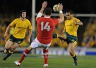 Australia&#39;s Will Genia from (right) kicks ahead during the second rugby union Test against Wales in Melbourne on June 16. Australia&#39;s Mike Harris kicked a penalty under huge pressure after the full-time siren to give the Wallabies a 25-23 win and break Welsh hearts