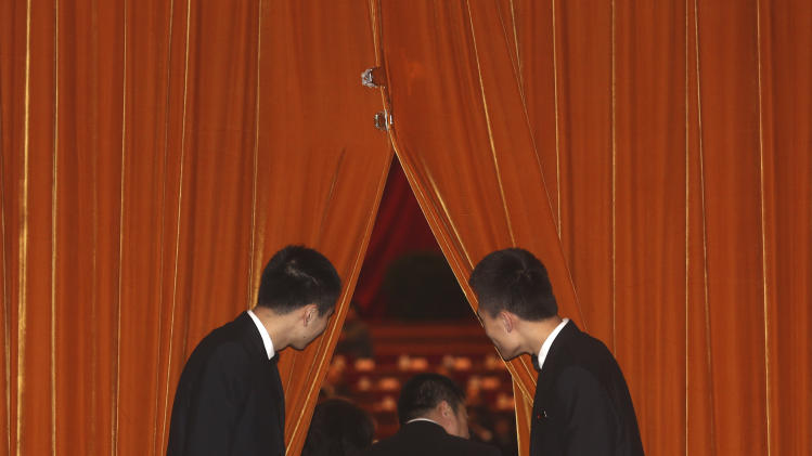 In this Friday, March 8, 2013 photo, Chinese soldiers dressed as ushers close curtains as a session of the National People's Congress is about to start inside the Great Hall of the People in Beijing. (AP Photo/Kin Cheung)