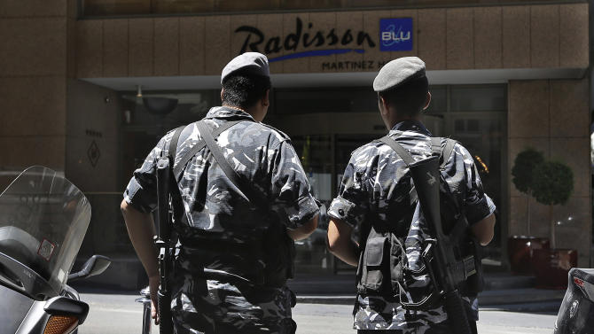Lebanese policemen stand guard outside a hotel where the rest of a Turkish Airlines crew stayed after six gunmen ambushed their vehicle on an old airport road and snatched two of the crewmembers, a pilot and a co-pilot, according to Lebanese officials, in Beirut, Lebanon, Friday, Aug. 9, 2013. (AP Photo/Hussein Malla)