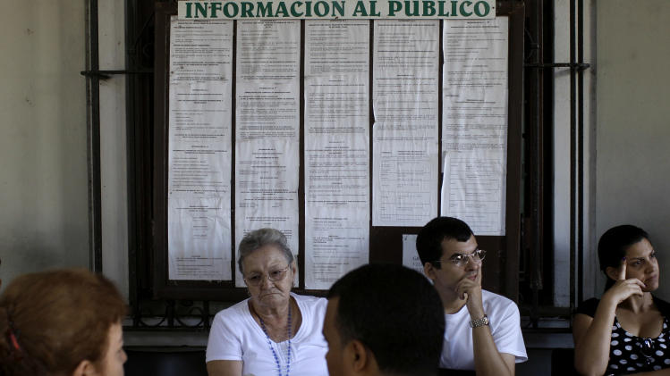 "In this Jan. 7, 2013 photo, people wait to apply for passports at an immigration office in Havana, Cuba. The overhaul of Cuba's decades-old migratory law, announced three months ago, is perhaps the most highly anticipated of a series of reforms initiated under President Raul Castro. It eliminates the hated ""white card"" exit visa that Cuba long forced its citizens to apply for before they could leave the island, something that led opponents to refer to the communist-run country as an ""island prison."" (AP Photo/Franklin Reyes)"
