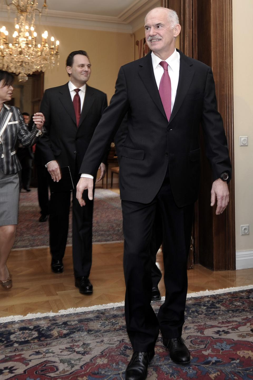 Greek Prime Minister George Papandreou, right, followed by the Foreign Minister Dimitris Droutsa arrive at the Presidential Palace  in Athens on Friday May 27, 2011.Greek political leaders held crisis meeting to find consensus on austerity measures. (AP Photo/Aris Messinis,pool)